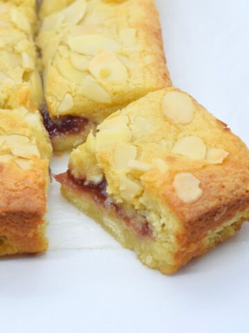 White chocolate bakewell blondies with a gooey jam middle and flaked almonds topping