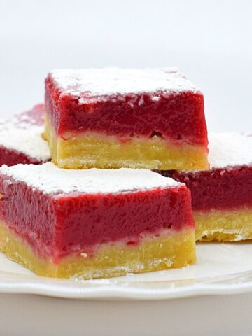 Raspberry dessert bars with a shortbread base and raspberry curd layer
