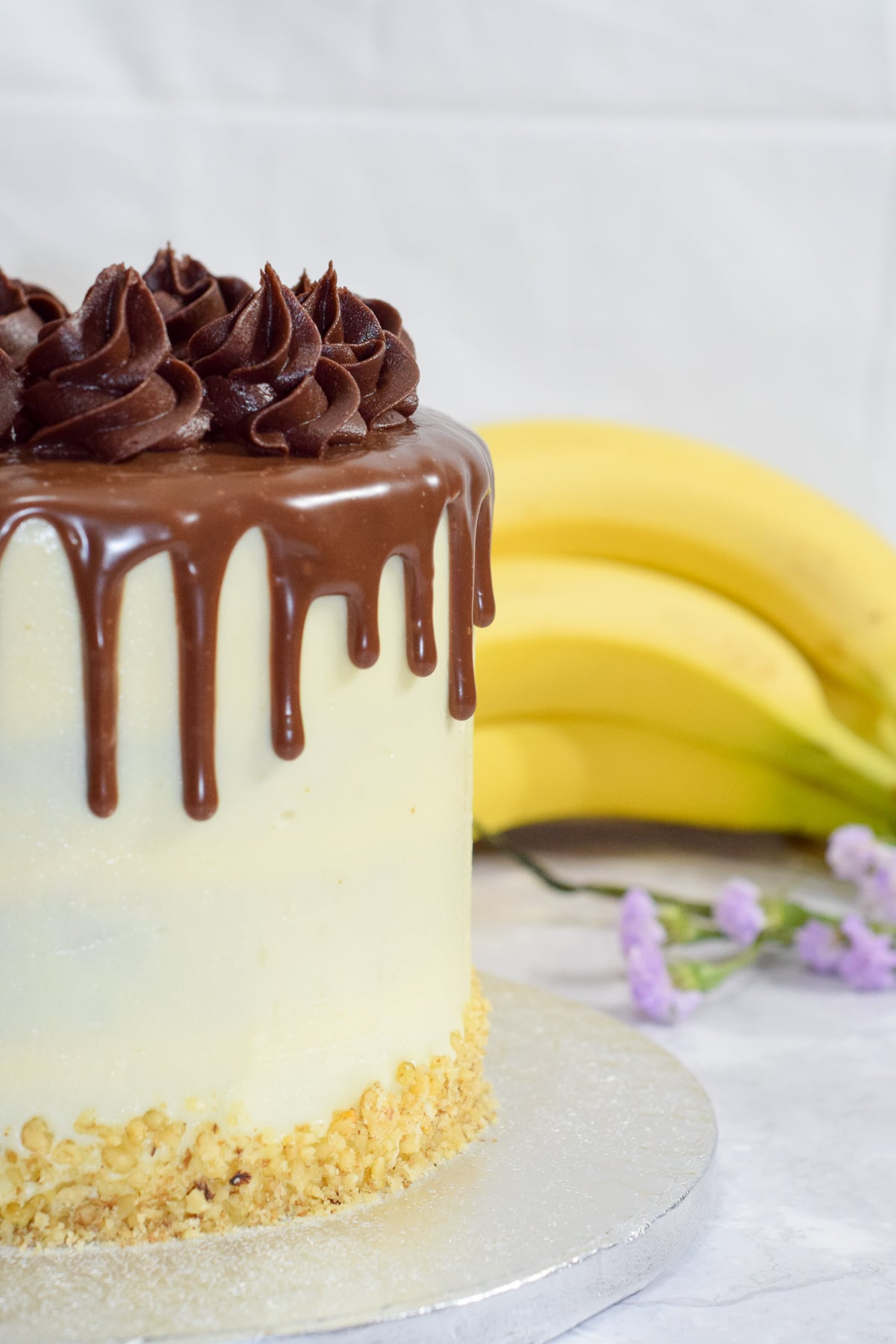 Banana walnut cake with vanilla cream cheese frosting and a milk chocolate ganache drip - side on view