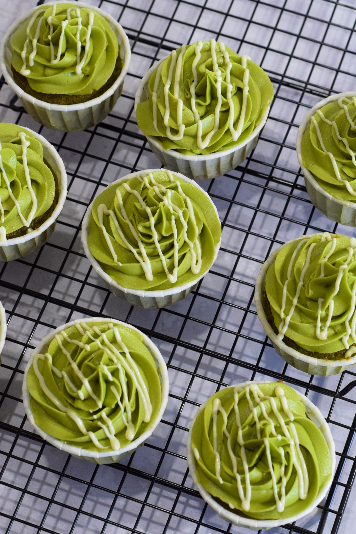 Matcha green tea cupcakes with a matcha buttercream frosting and white chocolate drizzle from above