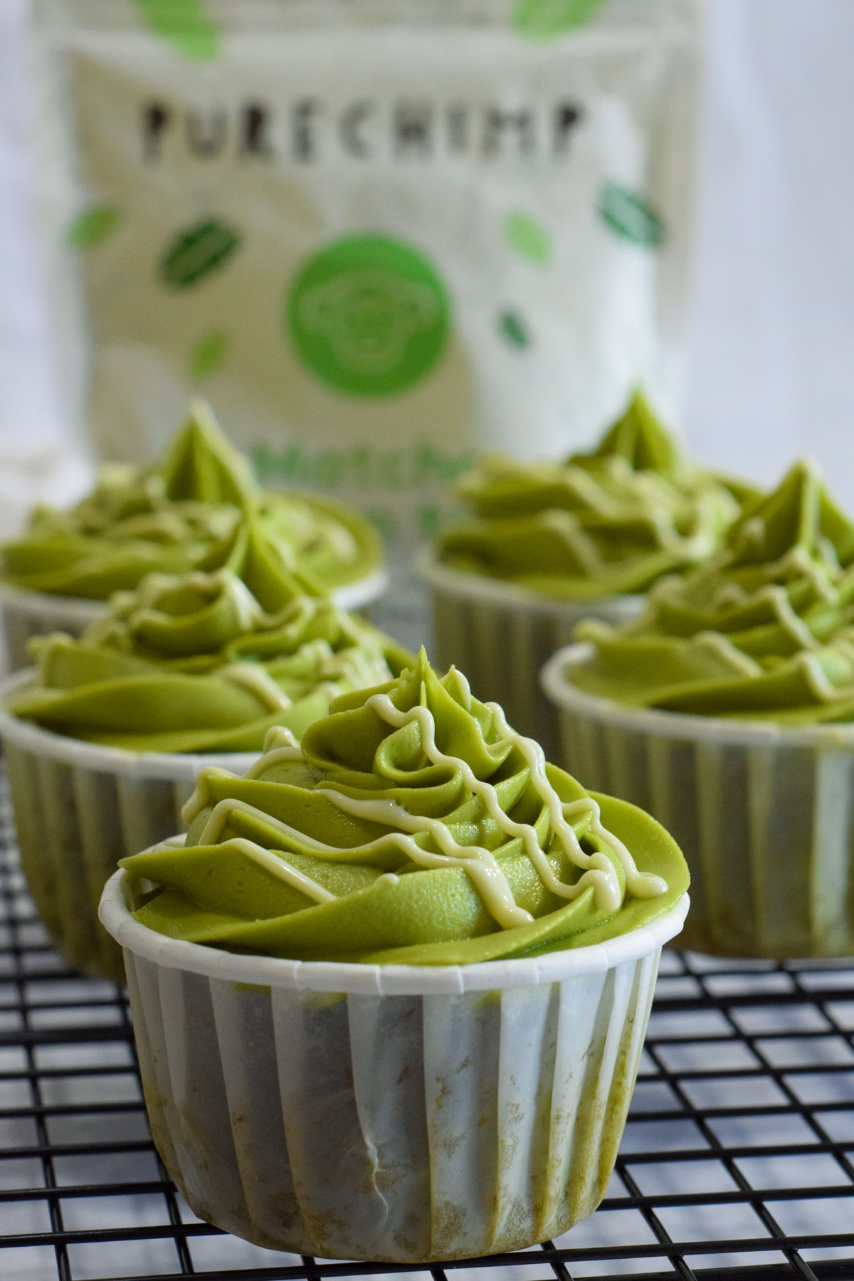 Matcha green tea cupcakes with a matcha buttercream frosting and white chocolate drizzle in white baking cups