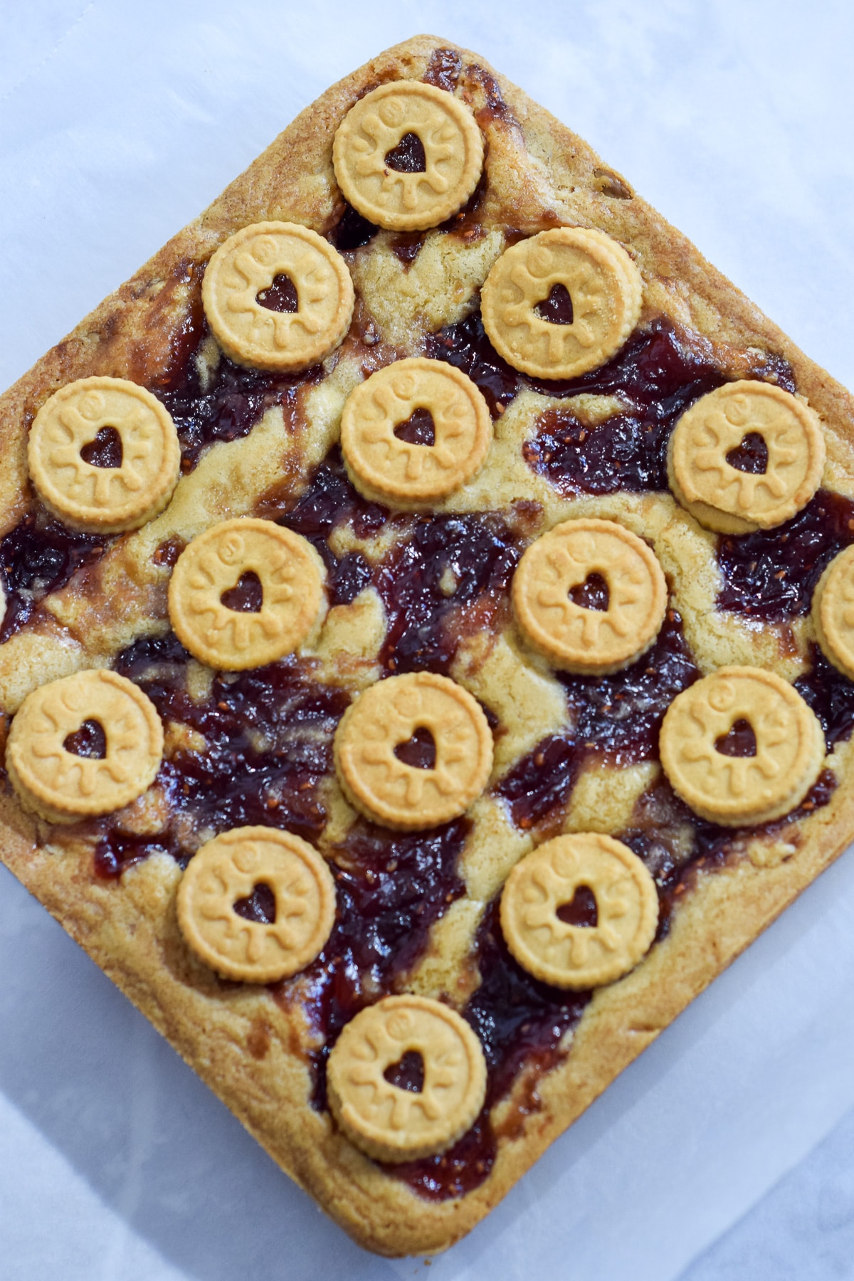 Mini Jammie Dodger blondies recipe with white chocolate chips and a jam swirl as a whole traybake