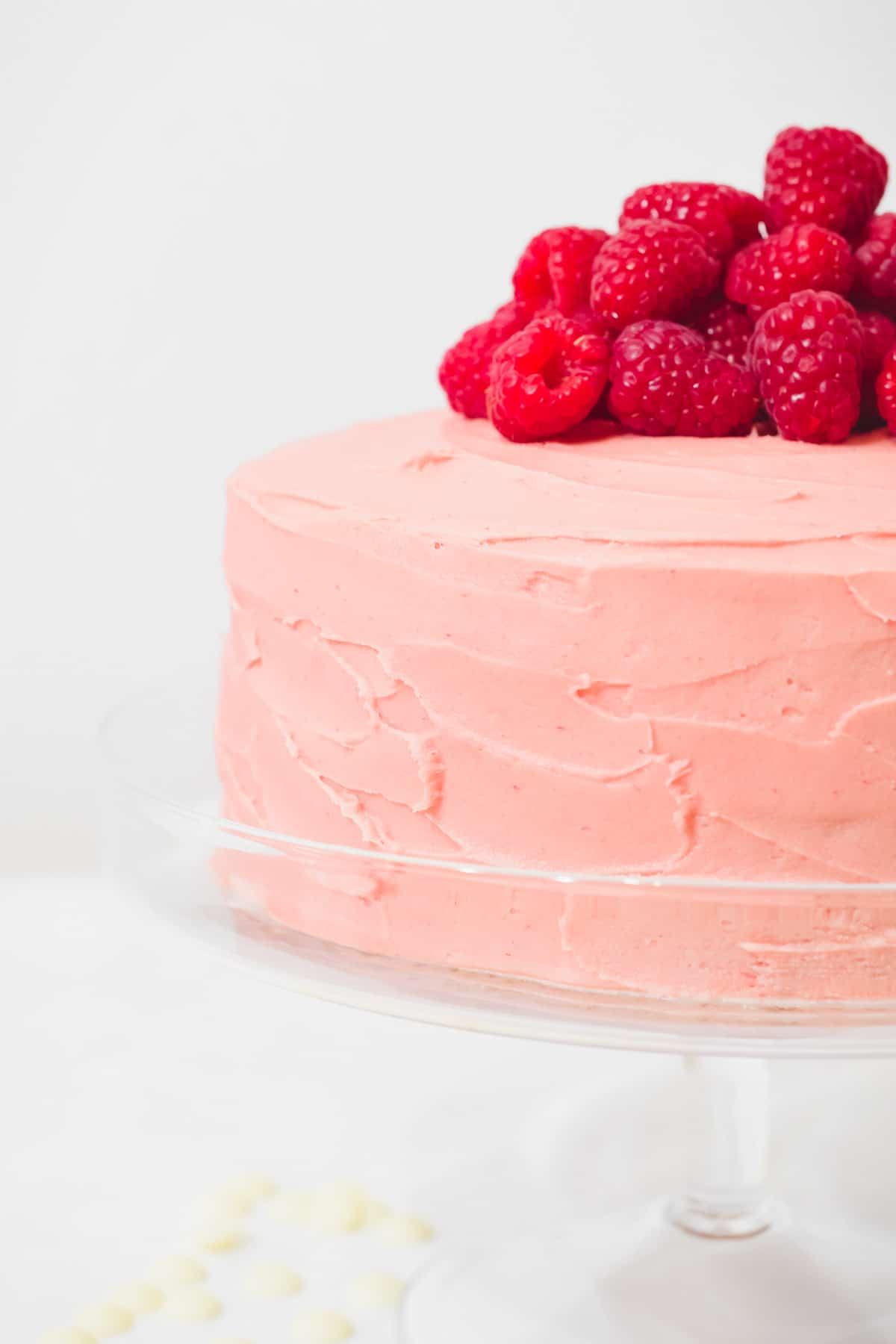 Side view of raspberry white chocolate cake with fresh raspberries piled on top