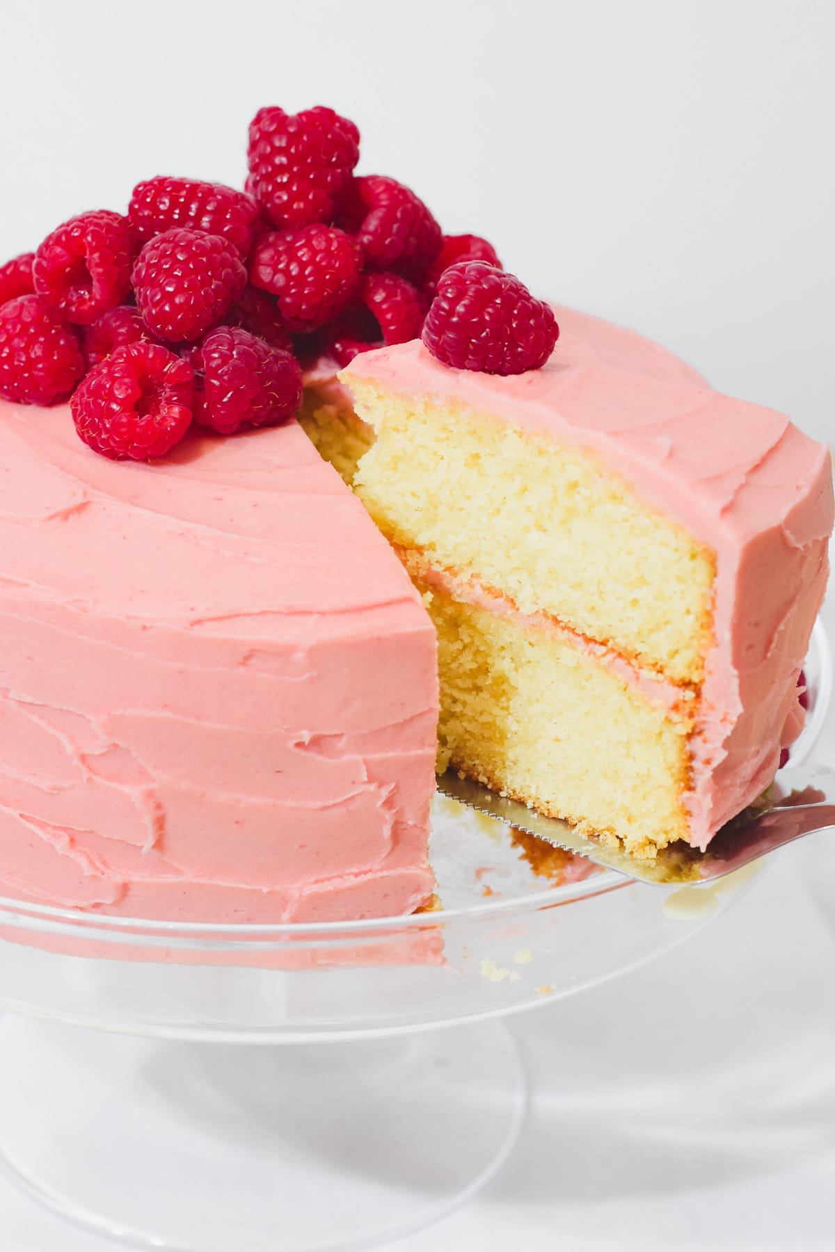 Raspberry white chocolate cake on a cake stand with a slice of cake being taken out