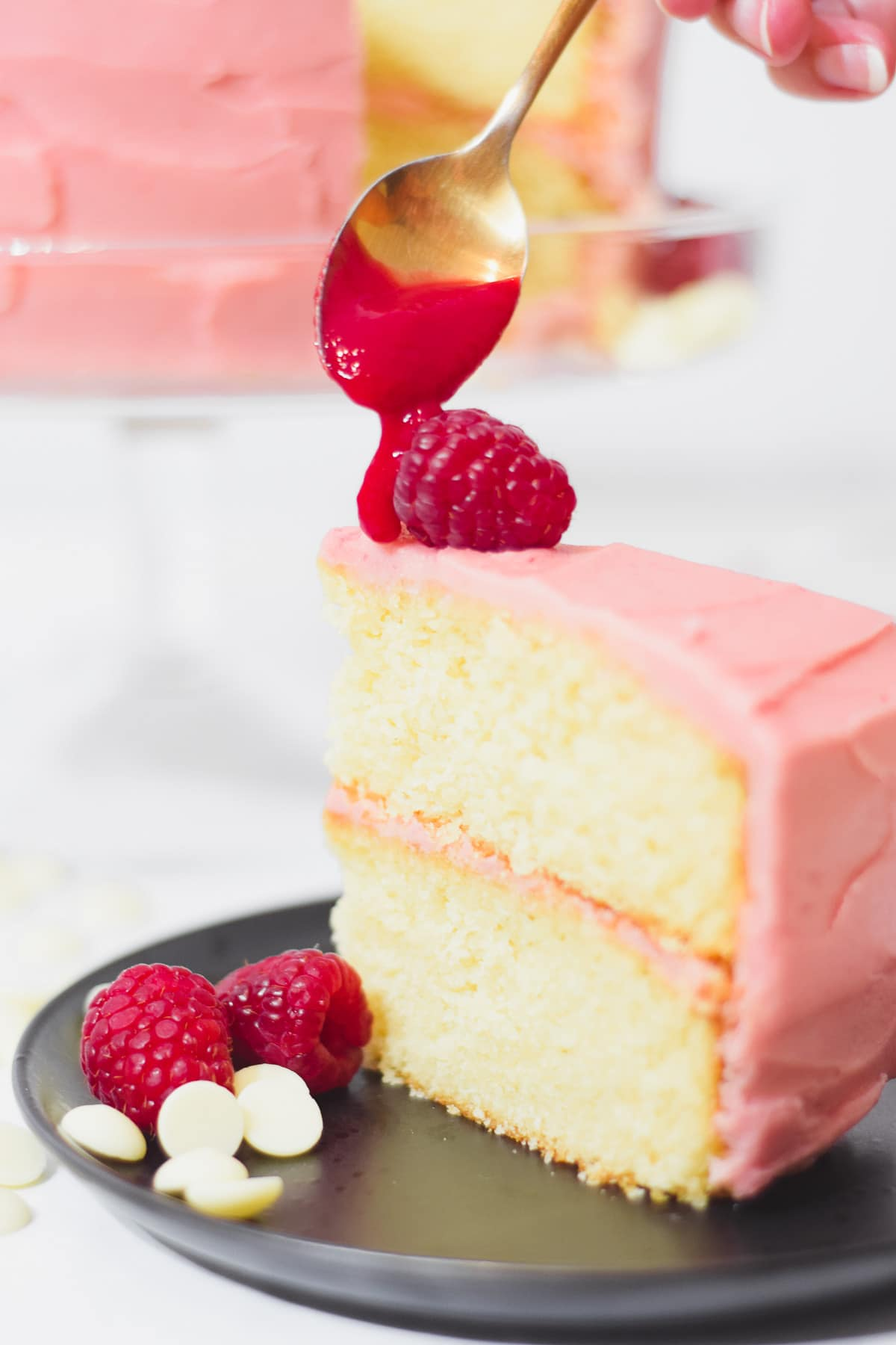 Slice of raspberry white chocolate cake with a pureed raspberry reduction being drizzled on top